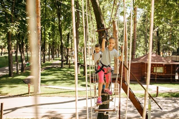 ロープパーク、遊び場での小さな女性登山家のレジャー。吊橋に登る子供