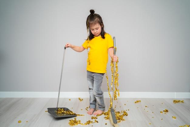 Маленький ребенок женского пола, уборка гостиной с метлой у себя дома. грустная девушка, держащая совок и венчик.