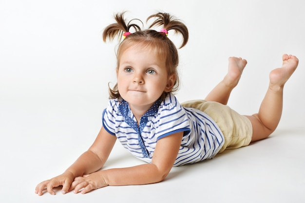 Little female kid with attractive look, dreamy expression, has two funny pony tails, raises legs upwards