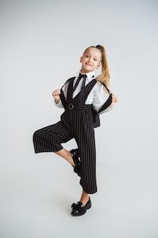 Маленькая женская модель позирует в школьной форме на белой стене студии