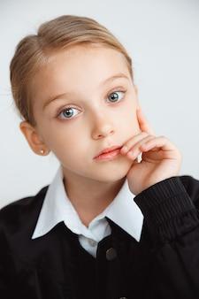 Little female model posing in school's uniform on white studio wall