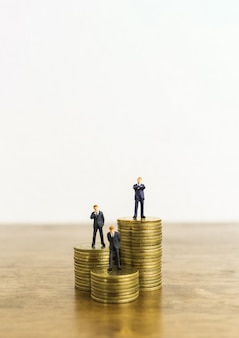 Little figure miniature businessman stand on stacks of coins.