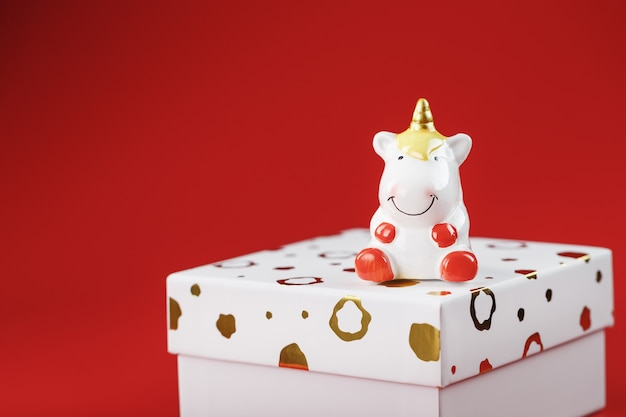 A little figure of a unicorn on the box with a gift on a red background