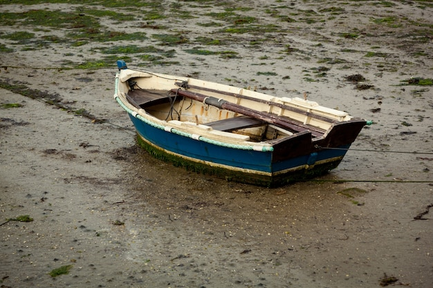 Little fishing boat stranded on the wet sand