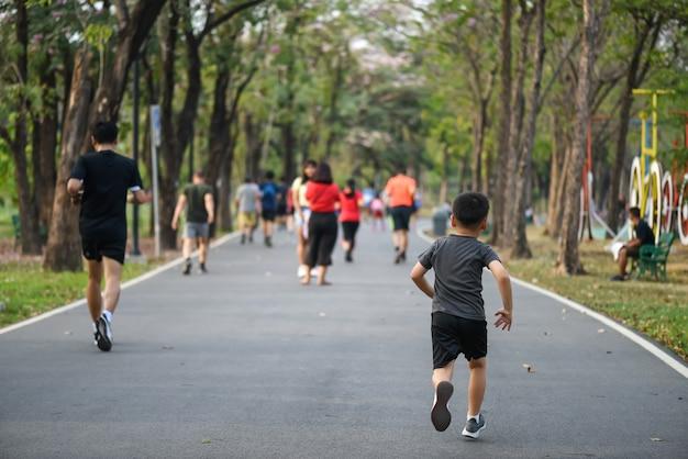 Маленький подтянутый азиатский мальчик быстро бегает по беговой дорожке в парке со многими взрослыми бегунами. бодибилдинг, детский спорт