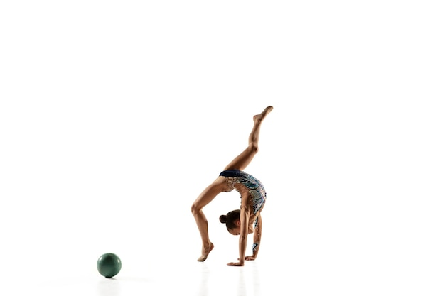 Little flexible female gymnast isolated on white wall