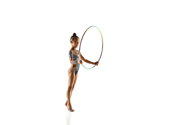 흰 벽에 고립 된 작은 유연한 소녀. 밝은 레오타드의 리듬 체조 아티스트로서의 작은 여성 모델. 모션, 액션, 스포츠의 품격. 후프로 운동하기.