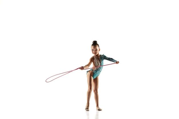 흰 벽에 고립 된 작은 유연한 소녀. 밝은 레오타드의 리듬 체조 아티스트로서의 작은 여성 모델. 모션, 액션, 스포츠의 품격. 줄넘기로 운동하기.