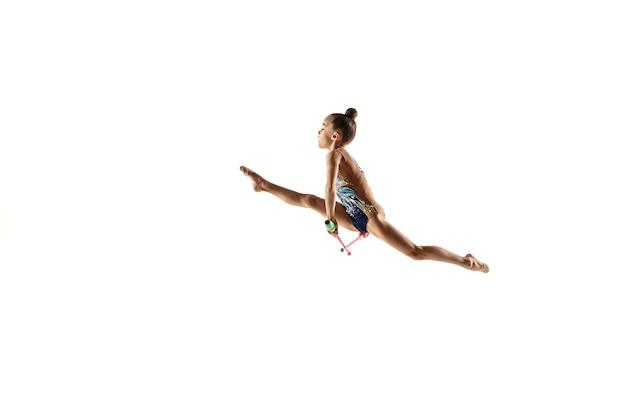 흰 벽에 고립 된 작은 유연한 소녀. 밝은 레오타드의 리듬 체조 아티스트로서의 작은 여성 모델. 모션, 액션, 스포츠의 품격. 메이스로 운동하기.