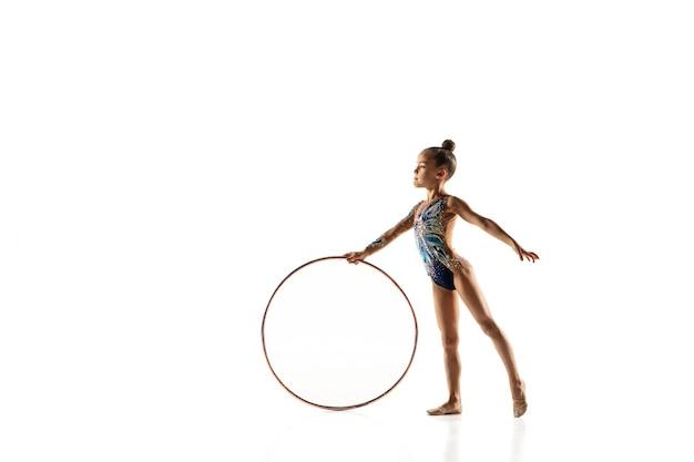 Piccola ragazza flessibile isolata su bianco. piccola modella femminile come artista di ginnastica ritmica in calzamaglia luminosa. g