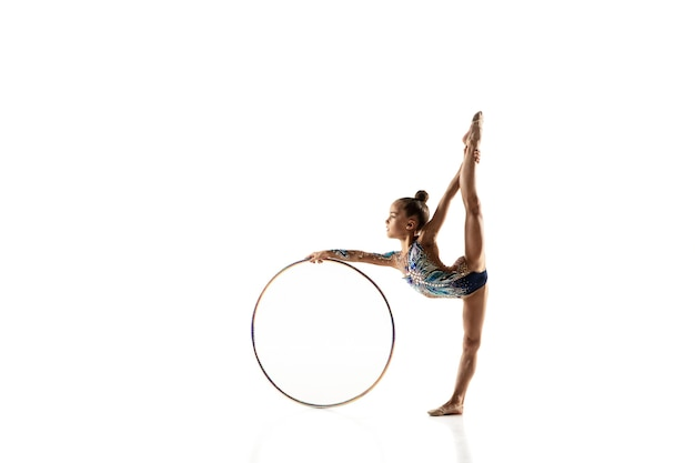 Piccola ragazza flessibile isolata su bianco. piccola modella femminile come artista di ginnastica ritmica in calzamaglia luminosa.