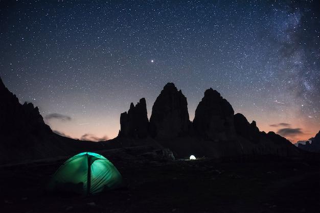 Небольшой туман над скалами. две осветительные палатки возле трех вершин горы тре чим в ночное время.