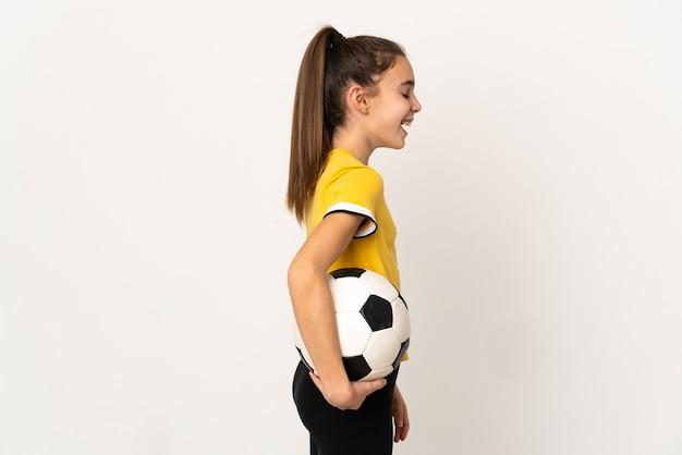 Маленькая девочка футболиста, изолированные на белом фоне, смеясь в боковом положении