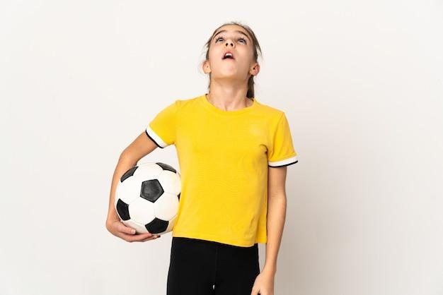 Маленькая девочка футболиста изолирована на белом фоне, глядя вверх и с удивленным выражением лица