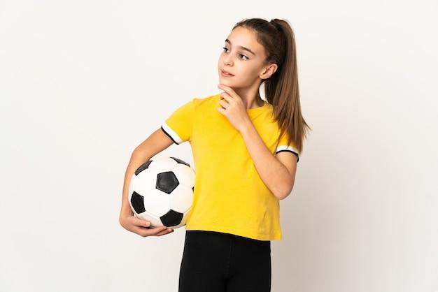 Маленькая девочка футболиста, изолированные на белом фоне, глядя вверх, улыбаясь