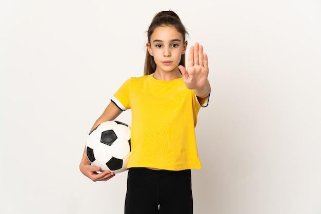 停止ジェスチャーを作る白い背景で隔離の小さなサッカー選手の女の子