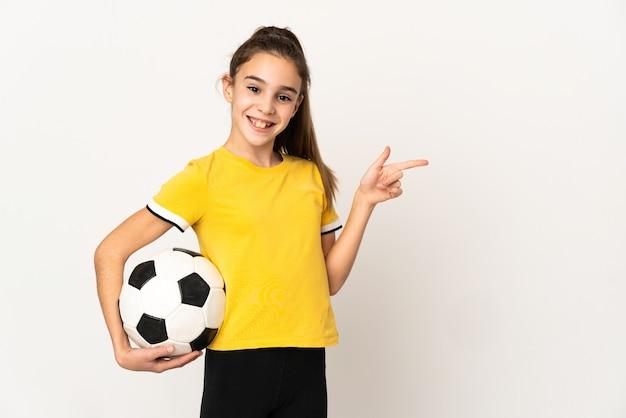 Маленькая девочка футболиста, изолированные на белом фоне, указывая пальцем в сторону