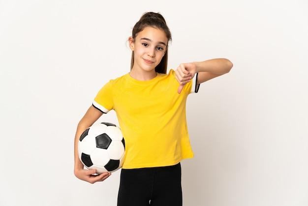 Маленькая девочка футболиста изолирована на белом фоне, показывая большой палец вниз с отрицательным выражением лица