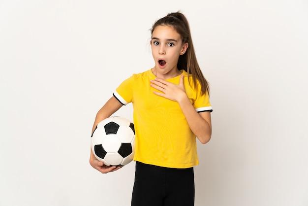 Маленькая девочка футболиста изолирована на белом фоне удивлена и шокирована, глядя вправо