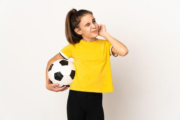 欲求不満と耳を覆っている白い壁に孤立した小さなサッカー選手の女の子