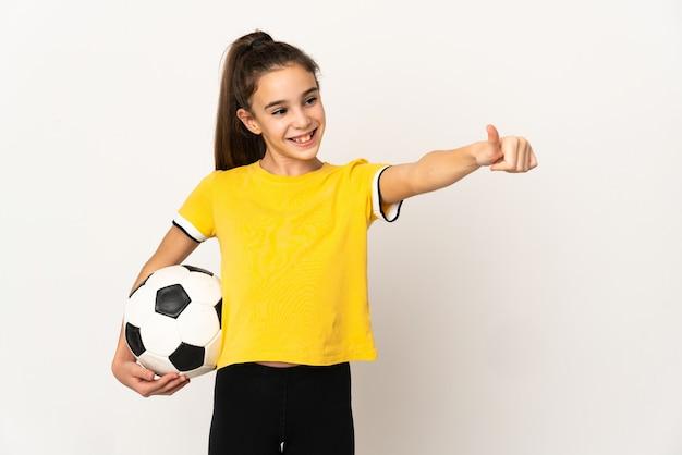 Маленькая девочка футболиста изолирована на белой стене, показывая большой палец вверх жест