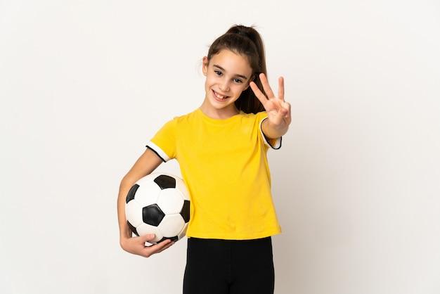 幸せな白い壁に孤立し、指で3を数える小さなサッカー選手の女の子