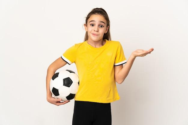 Маленькая девочка футболиста изолирована на белой стене, сомневаясь, поднимая руки