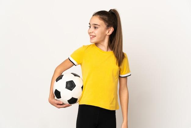Маленькая девочка футболиста изолирована на белой стене, глядя в сторону и улыбается