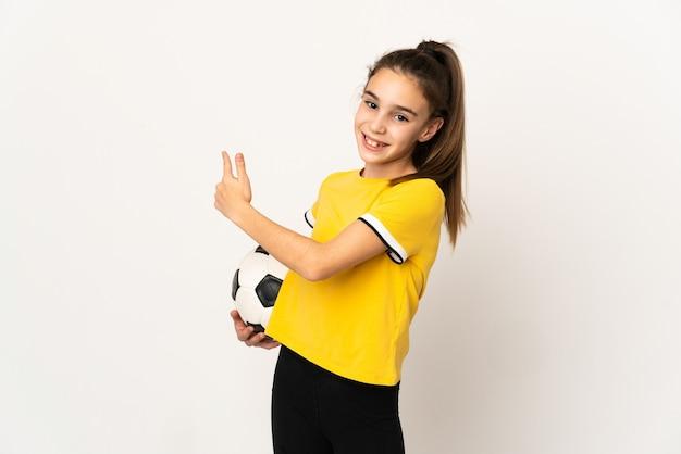 Маленькая девочка футболиста изолирована на белой стене, указывая назад