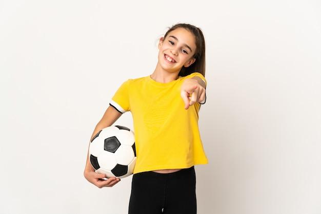 Маленькая девочка футболиста изолирована на белой стене, указывая вперед с счастливым выражением лица
