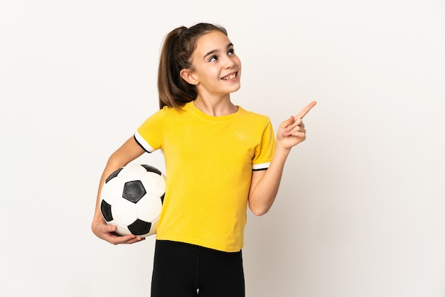 Маленькая девочка футболиста изолирована на белой стене, указывая вверх отличную идею