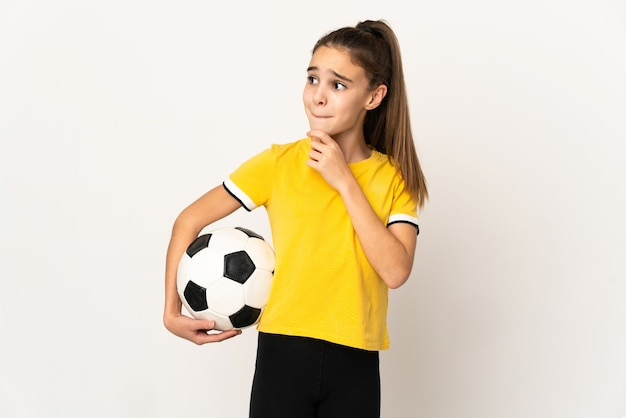 Little football player girl isolated on white background having doubts and thinking