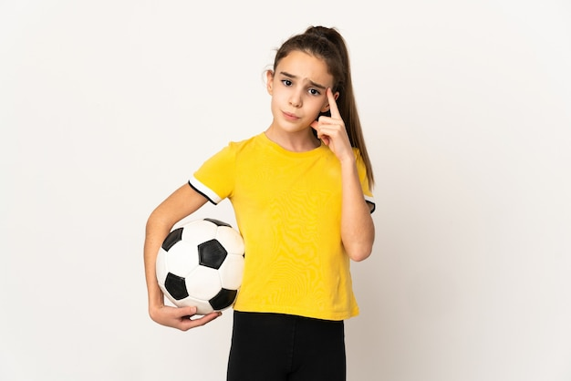 Little football player girl isolated on white background thinking an idea