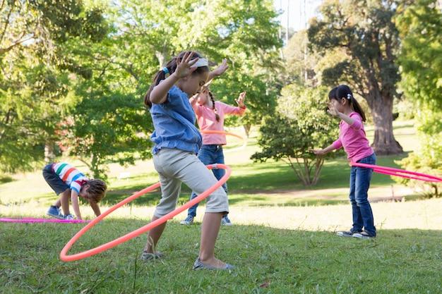 Маленькие друзья, играющие с обручами в парке