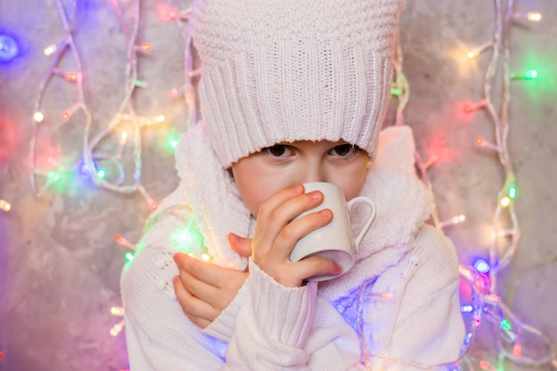 Little frozen girl in a white knitted sweater and hat drinks from a cup a hot warming drink against the background of a colored garland. the concept of cold and warming