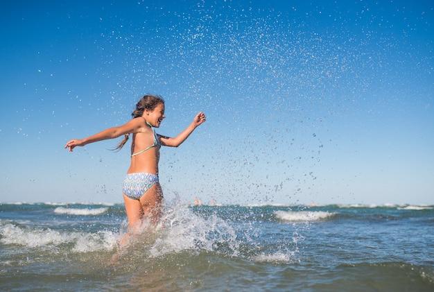Маленькая забавная активная счастливая девушка плещется в шумных морских волнах в солнечный теплый летний день