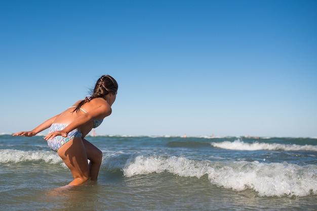화창한 따뜻한 여름날에 시끄러운 바다 파도에 튀는 작은 재미 활성 행복 소녀
