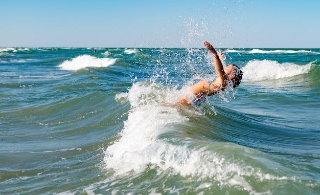 晴れた暖かい夏の日に騒々しい海の波に飛び散る小さな面白いアクティブな幸せな女の子