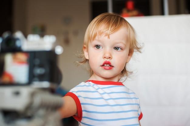 少し面白いブロンドの赤ちゃんの少女は、カメラを見てください。似たようなカメラの姿勢を学ぶ