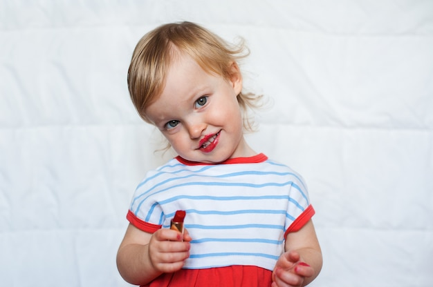 Little funny blond baby girl make up lips with mom's red lipstick. learning to be woman.