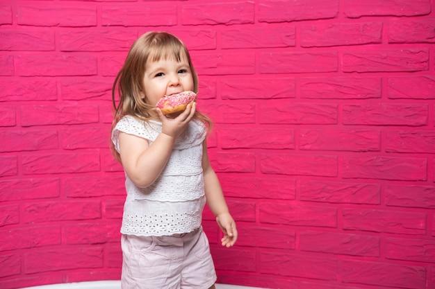 흰 셔츠에 작은 재미있는 금발 소녀 분홍색 배경에 도넛을 먹는다.