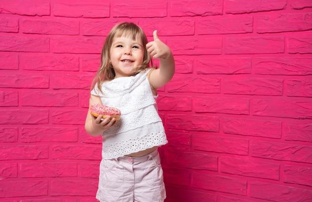흰 셔츠에 재미 있은 금발 소녀 핑크에 도넛을 먹는다