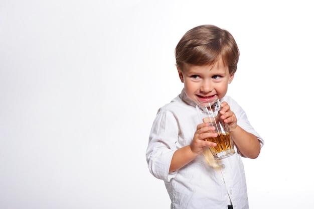Маленький смешной мальчик, пить свежий сок