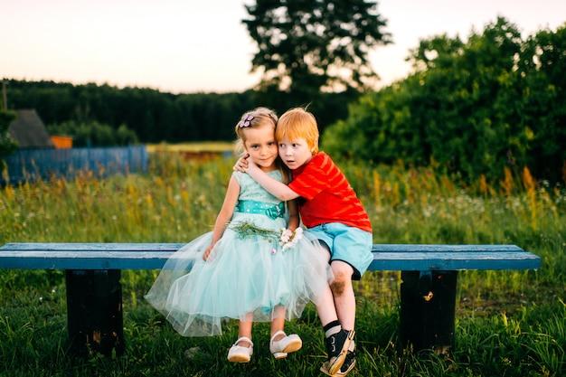 面白い少年はドレスで恥ずかしがり屋の美しい少女を抱擁します。