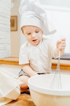 パンケーキ生地で泡立て器を保持しているクックスーツの小さな面白い男の子