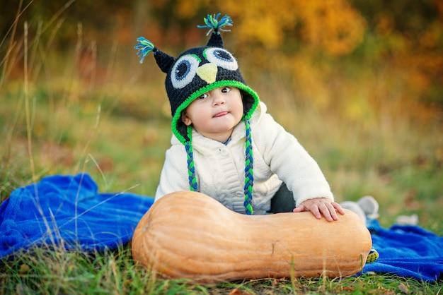 ニットキャップの面白い少年は、カボチャと秋の木々と草の上に座って、舌を示しています