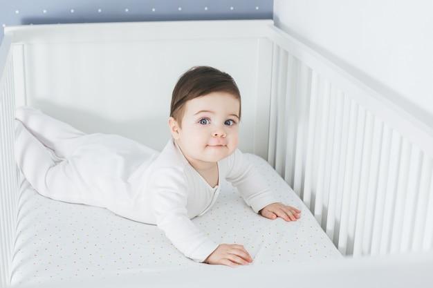 아기 침대에 누워 웃 고 재미있는 소년