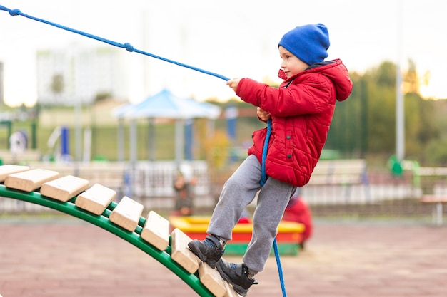 A little funny boy in a warm red jacket and hat climbs a wooden slide using a rope at a playground in a city park.