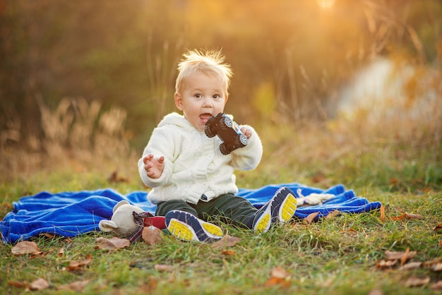 Little funny boy with sticking up hair sitting on a blue plaid on green lawn and playing with toys at sunset.