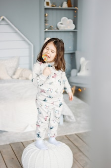 Little funny brunette girl in cozy pajamas with lollipop in children bed room